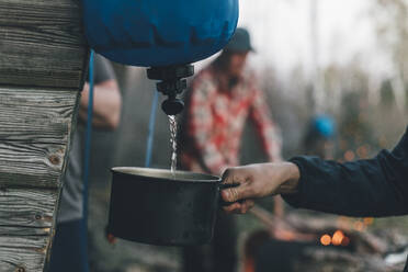 Person filling skillet with water in an outdoor camp - GUSF03728