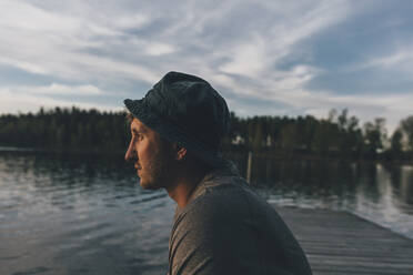 Young man with hat, looking at lake - GUSF03746