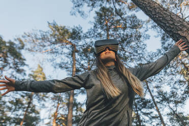 Young woman using VR goggles in nature - GUSF03767