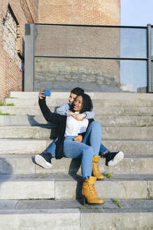 Mother and son sitting together on steps taking selfie with smartphone - DGOF00915