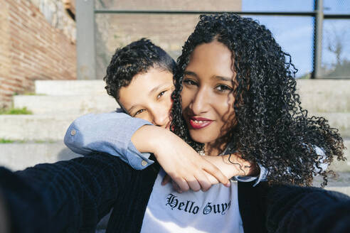 Portrait of happy mother and son sitting together on steps taking selfie - DGOF00918