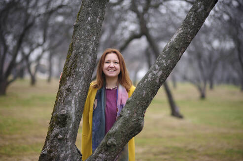 Portrait of smiling woman standing against bare tree in park - EYAF01045