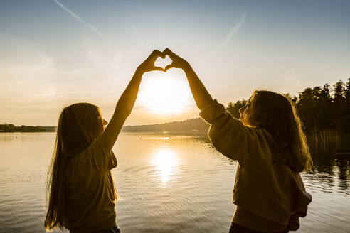 Friends making heart shape with hands against lake during sunset - OJF00393