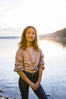 Smiling girl standing at lakeshore against sky during sunset - OJF00399