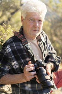 Portrait of senior man with camera in nature - AFVF06129