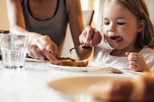 Portrait of little girl watching her mother spreading chocolate cream on croissant - WFF00374
