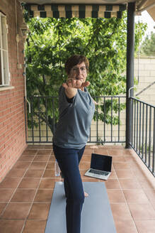 Senior woman practising yoga with laptop on balcony - XLGF00065