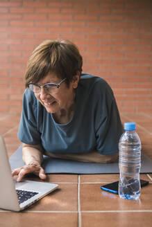 Senior woman using laptop on balcony - XLGF00068