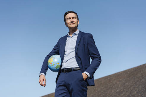Mature businessman holding a globe on a disused mine tip - JOSEF00384