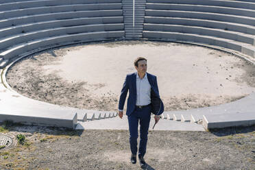 Mature businessman at an amphitheatre on a disused mine tip site - JOSEF00396