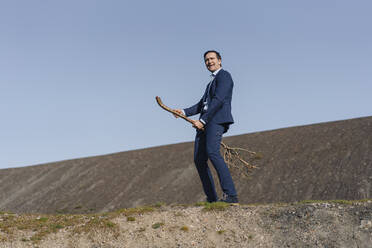 Mature businessman riding a bare tree on a disused mine tip - JOSEF00405
