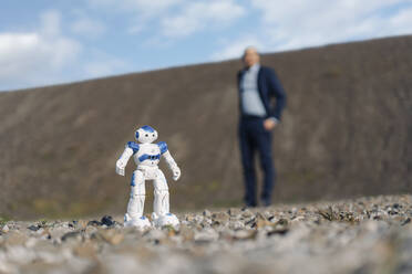 Miniature robot and businessman on a disused mine tip - JOSEF00414
