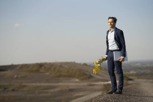 Mature businessman holding bunch of flowers and laptop on a disused mine tip - JOSEF00432