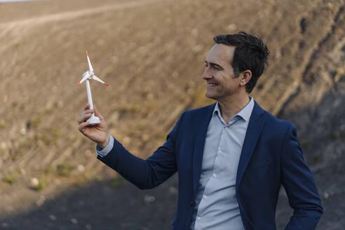 Happy mature businessman on a disused mine tip holding wind turbine model - JOSEF00438