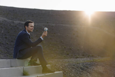 Mature businessman holding a miniature globe on a disused mine tip - JOSEF00447