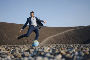 Mature businessman playing soccer with a globe on a disused mine tip - JOSEF00465