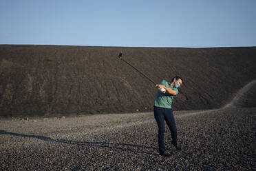 Mature man with a mask playing golf on a disused mine tip - JOSEF00468