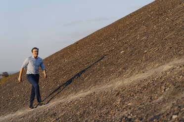 Mature businessman walking on a disused mine tip - JOSEF00480