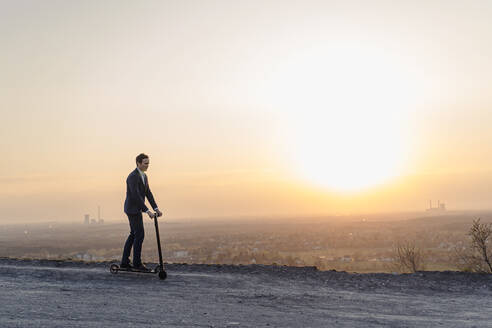 Mature businessman riding a kick scooter on a disused mine tip at sunset - JOSEF00489