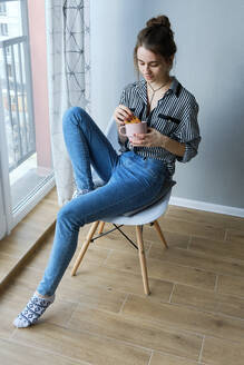 Millennial brown-haired girl drinking tea with cakes alone - CAVF79922
