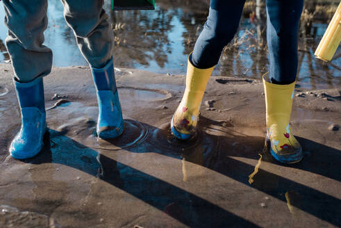 Children's rain boots playing In the sand and sea in Sweden - CAVF79943