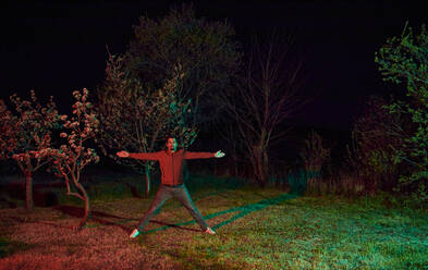 Man with arms outstretched standing in garden at night - ZEDF03316
