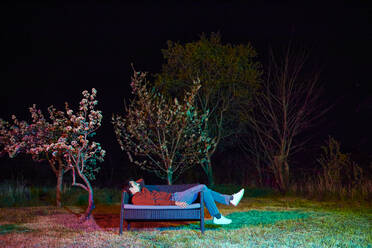 Sad man sitting alone on garden bench at night - ZEDF03319