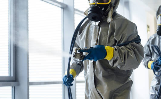 Cleaning staff desinfecting hospital against contageous virus, wearing protective clothing - JCMF00599