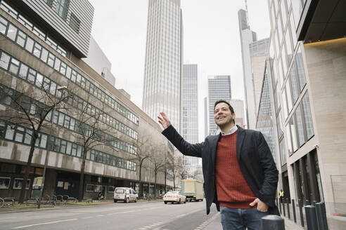 Smiling mid adult businessman hailing taxi while standing on sidewalk in city, Frankfurt, Germany - AHSF02357