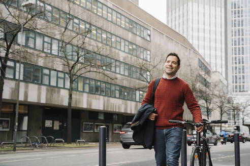 Smiling businessman looking away while walking with bicycle by road in Frankfurt, Germany - AHSF02369