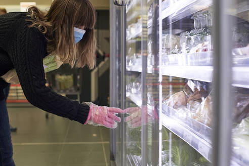 Woman wearing mask choosing vegetables in refrigerated section at supermarket - VEGF01969