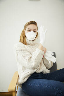 Portrait of blond woman wearing FFP2 mask at home - FSF01032