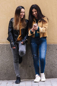 Beautiful women using a mobile at the Street. LGTB concept - CAVF80128
