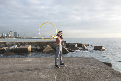 Happy woman playing with hula hoop at harbour - XLGF00077