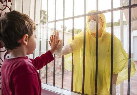 Boy touching mother's hand wearing protective clothing behind windowpane - LJF01513
