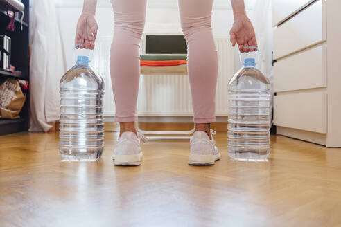 Low section of woman practicing weightlifting with water bottles at home - JCMF00650