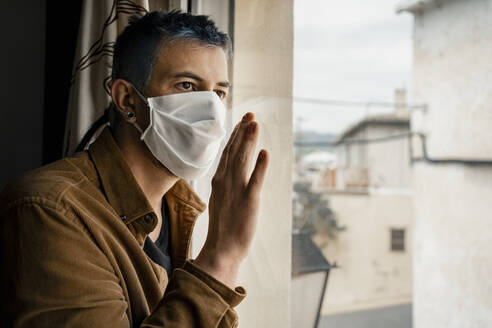 Man wearing protective mask and looking out of the window - RCPF00233