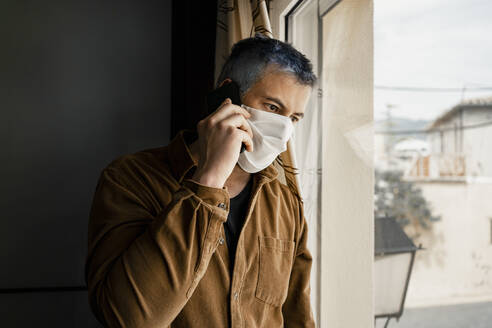 Man wearing protective mask and looking out of the window - RCPF00236