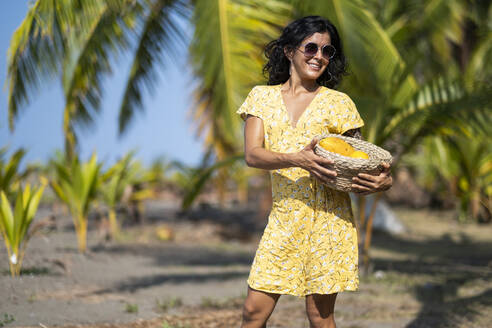 Young woman holding a fruit basket at the beach, Costa Rica - AMUF00098