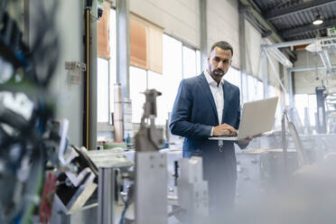 Businessman using laptop in a factory - DIGF09946
