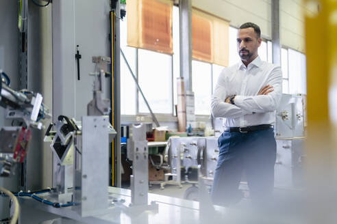 Businessman looking at modern machine in a factory - DIGF09949