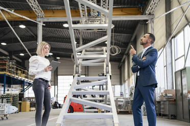 Businessman and young woman with tablet talking in a factory - DIGF09961