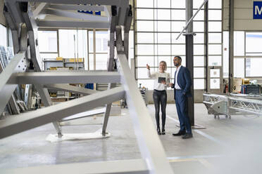 Businessman and young woman talking in a factory - DIGF09964