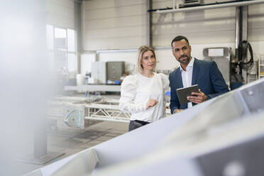 Portrait of businessman with tablet and young woman in a factory - DIGF09967
