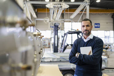 Portrait of a confident businessman holding tablet in a factory - DIGF09976