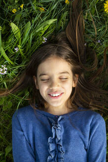 Portrait of girl with eyes closed relaxing on a meadow in spring - LVF08850