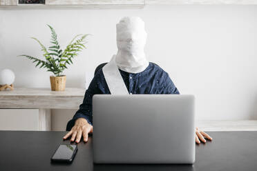 Man working at home with his head covered in toilet paper - JRFF04399