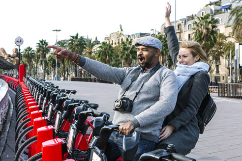 Happy couple at bike share stand in city, Barcelona, Spain - XLGF00087