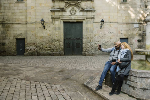 Couple taking selfie with smartphone at Sant Felip Neri Square, Barcelona, Spain - XLGF00099