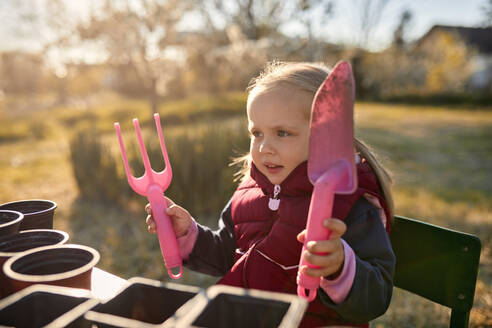 Portrait of girl holding gardening tools - ZEDF03323
